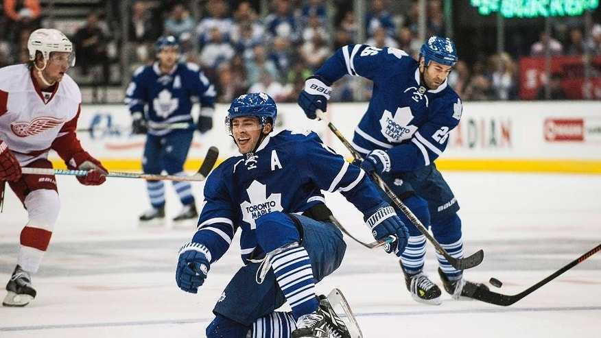 Toronto Maple Leafs' Joffrey Lupul, center, recovers from a check against the Detroit Red Wings during second-period preseason NHL hockey game action in Toronto, Friday, Oct. 3, 2014. (AP Photo/The Canadian Press, Aaron Vincent Elkaim)