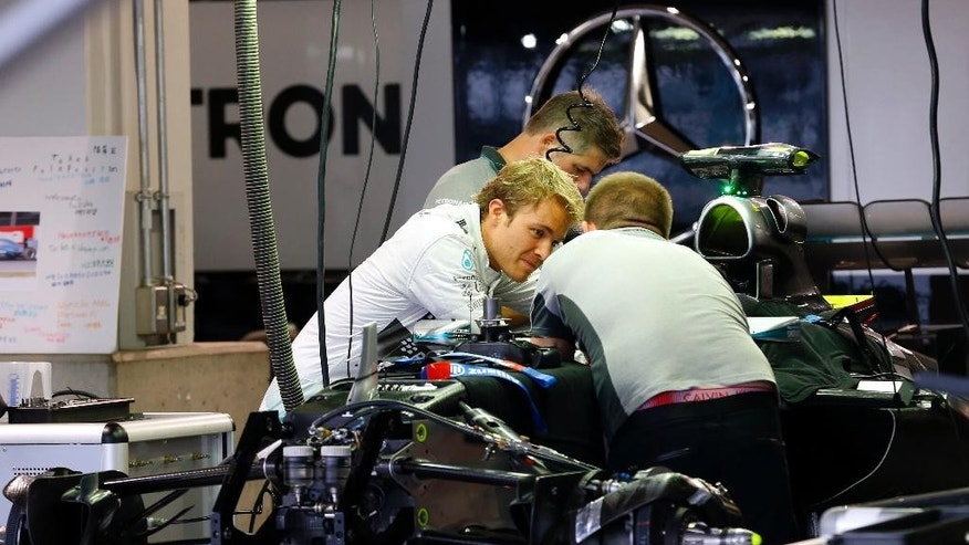 Mercedes driver Nico Rosberg of Germany talks to mechanics at his team's garage at the Suzuka Circuit in Suzuka, central Japan, Thursday, Oct. 2, 2014 ahead of Sunday's Japanese Formula One Grand Prix. (AP Photo/Shizuo Kambayashi)