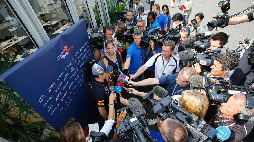 Toro Rosso driver Max Verstappen of the Netherlands is surrounded by journalists after his first practice session for Sunday's Japanese Formula One Grand Prix at the Suzuka Circuit in Suzuka, central Japan, Friday, Oct. 3, 2014. Verstappen said he was satisfied with his performance at the Japanese Grand Prix on Friday where he became the youngest driver to take part in a Formula One Grand Prix weekend. (AP Photo/Shizuo Kambayashi)