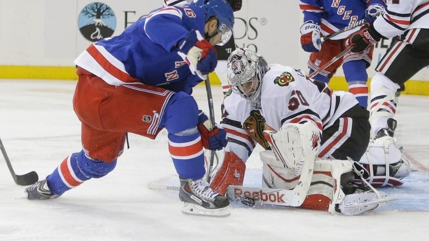 Chicago Blackhawks goalie Corey Crawford (50) stops a shot on the goal by New York Rangers' Derick Brassard (16) during the second period of an NHL preseason hockey game Friday, Oct. 3, 2014, in New York. (AP Photo/Frank Franklin II)