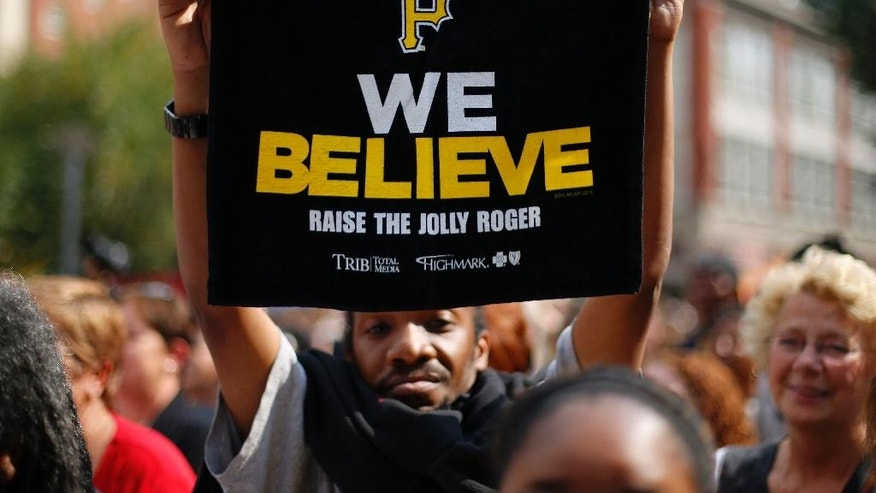 A Pittsburgh Pirates fan holds up a towel handed out at a Pirates pep rally in downtown Pittsburgh Tuesday, Sept. 30, 2014. The Pirates face the San Francisco Giants in the wild card game in Pittsburgh Wednesday night. (AP Photo/Gene J. Puskar)