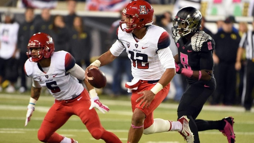 Arizona quarterback Anu Solomon (12) runs with the ball during the second quarter of an NCAA college football game against Oregon on Thursday, Oct. 2, 2014, in Eugene, Ore. (AP Photo/Steve Dykes)
