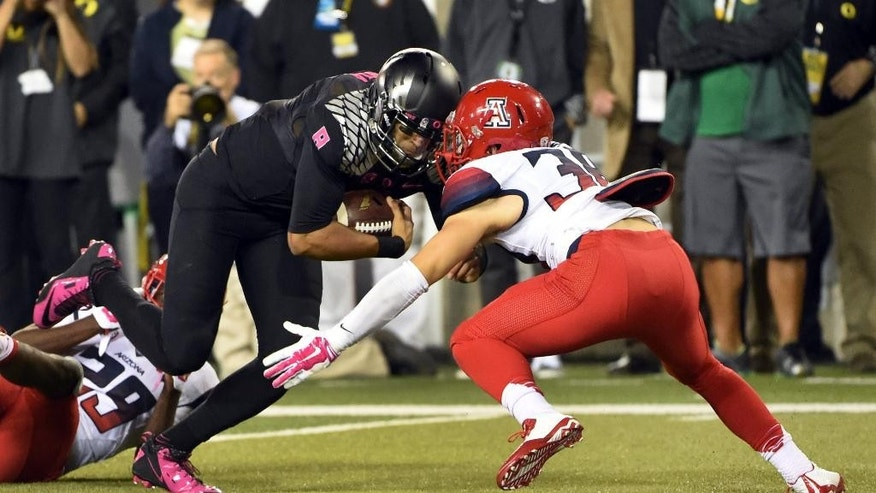 Oregon quarterback Marcus Mariota (8) runs for a touchdown as Arizona safety Jared Tevis (38) closes in during the second quarter of an NCAA college football game Thursday, Oct. 2, 2014, in Eugene, Ore. (AP Photo/Steve Dykes)