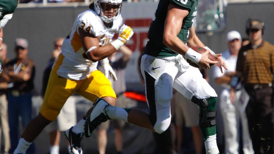 Michigan State quarterback Connor Cook (18) scrambles against Wyoming's Siaosi Hala'api'api during the first quarter of an NCAA college football game, Saturday, Sept. 27, 2014, in East Lansing, Mich. Michigan State won 56-14. (AP Photo/Al Goldis)