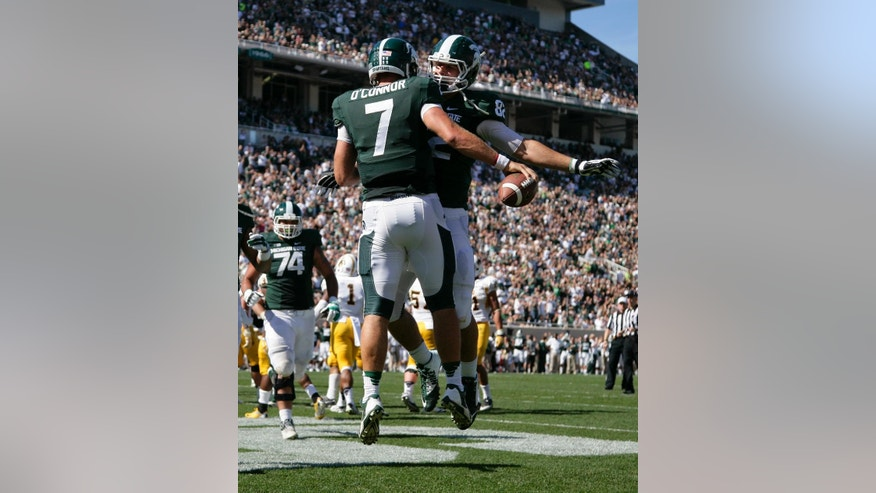 Michigan State's Tyler O'Connor (7) and Josiah Price celebrate O'Connor's touchdown during the fourth quarter of an NCAA college football game against Wyoming, Saturday, Sept. 27, 2014, in East Lansing, Mich. Michigan State won 56-14. (AP Photo/Al Goldis)