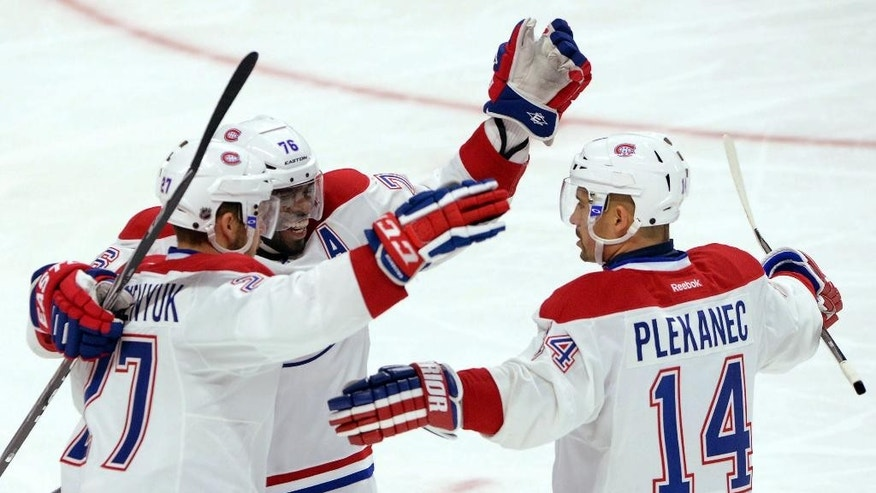 Montreal Canadiens' P.K. Subban, middle, and Tomas Plekanec, right, congratulates Alex Galchenyuk on his second-period goal against the Ottawa Senators during a preseason NHL hockey game in Ottawa, Ontario, on Friday, Oct. 3, 2014. (AP Photo/The Canadian Press, Sean Kilpatrick)