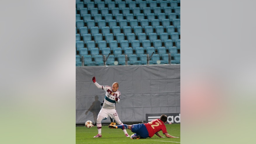 Bayern's Arjen Robben, left is tackled by CSKA's Georgi Schennikov during the Champions League Group E soccer match between CSKA Moscow and Bayern Munich at the Arena Khimki stadium in Moscow, Russia, Tuesday Sept. 30, 2014. CSKA are playing in an empty stadium after being sanctioned by the governing body UEFA for the behaviour of their fans during group stage matches against Manchester City and Czech club Viktoria Plzen last season. (AP Photo/Ivan Sekretarev)
