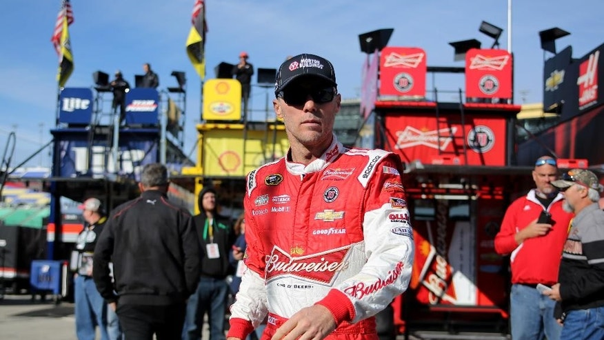 NASCAR auto racing driver Kevin Harvick walks to his car as he prepares to take practice laps for the Sprint Cup Series Hollywood Casino 400 at Kansas Speedway, Saturday, Oct. 4, 2014, in Kansas City, Kan. Harvick took the pole for Sunday's race. (AP Photo/Ed Zurga)