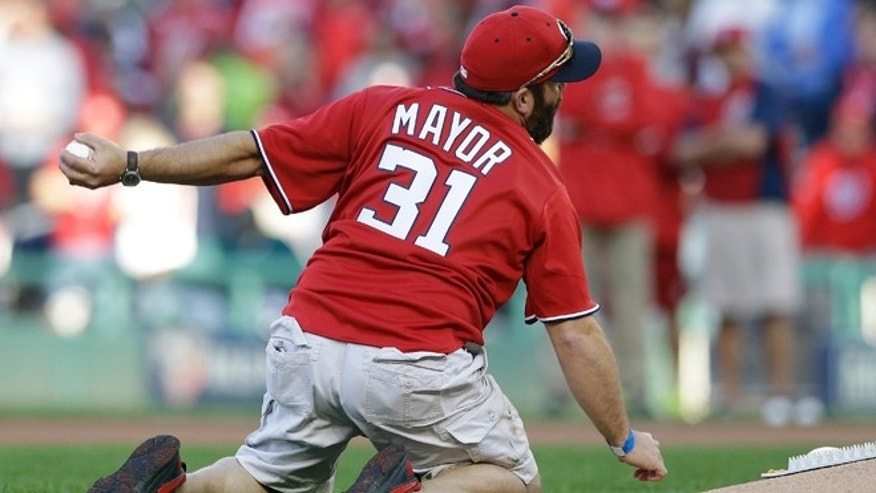 Oct 4., 2014: U.S. Army Sgt. 1st Class Brian Keaton, mimics a grenade toss for the ceremonial first pitch before Game 2 of baseball's NL Division Series between the Washington Nationals and the San Francisco Giants in Nationals Park in Washington. (AP)