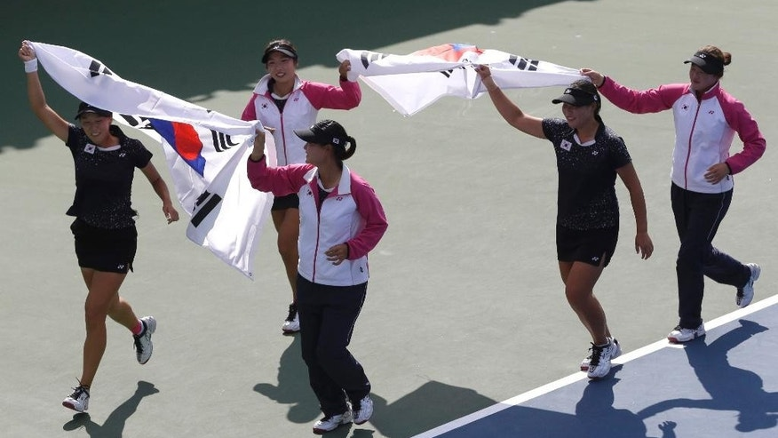 South Korea's team celebrate after defeating Japan to win the gold medal during their Women's Team soft tennis final match at the 17th Asian Games in Incheon, South Korea, Saturday, Oct. 4, 2014. (AP Photo/Dita Alangkara)