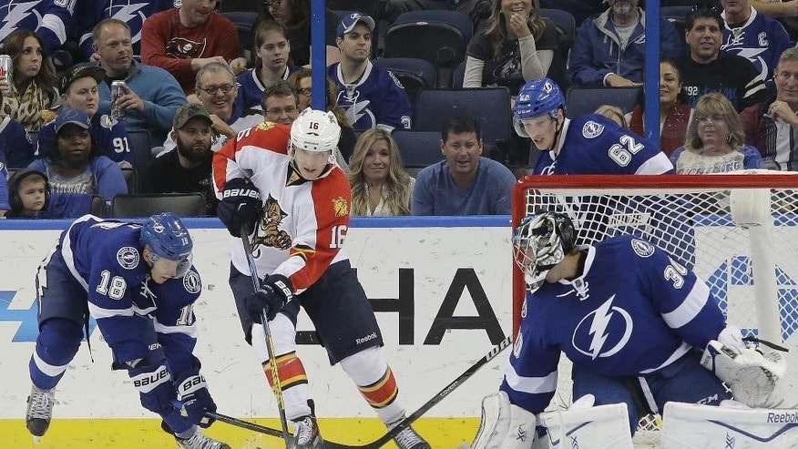 Florida Panthers center Aleksander Barkov (16) moves the puck around Tampa Bay Lightning left wing Ondrej Palat (18) and goalie Ben Bishop (30) during the second period of an NHL preseason hockey game Saturday, Oct. 4, 2014, in Tampa, Fla. (AP Photo/Chris O'Meara)