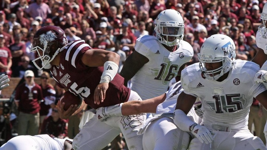 Mississippi State quarterback Dak Prescott (15) breaks through Texas A&M defenders including linebacker Donnie Baggs (16) and defensive lineman Myles Garrett (15) to score a touchdown during the second half of an NCAA college football game in Starkville, Miss., Saturday, Oct. 4, 2014. No. 12 MSU won 48-31.(AP Photo/Jim Lytle)