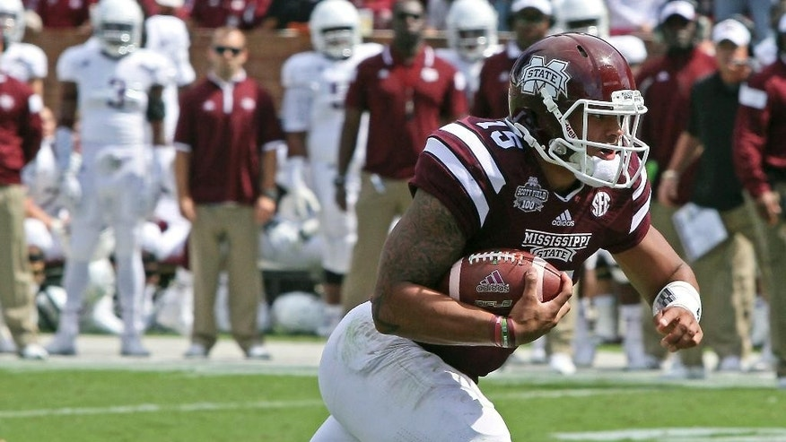 Mississippi State quarterback Dak Prescott (15) gains additional yardage after receiving a pass during the first half of an NCAA college football game against Texas A&M in Starkville, Miss., Saturday, Oct. 4, 2014. (AP Photo/Jim Lytle)