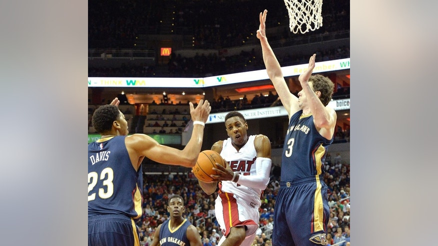 Miami Heat's Mario Chalmers, center, drives the lane against the defense of New Orleans Pelicans' Anthony Davis, left, and Omar Asik during the first half of an NBA basketball preseason game in Louisville, Ky., Saturday, Oct. 4, 2014. (AP Photo/Timothy D. Easley)