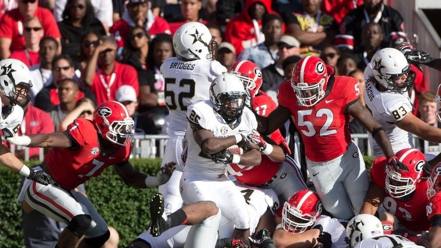 Vanderbilt running back Ralph Webb (26) escapers from the Georgia defenders Lorenzo Carter (7) and linebacker Amarlo Herrera (52) to score a touchdown in the first half of an NCAA college football game Saturday, Oct. 4, 2014, in Athens, Ga. (AP Photo/John Bazemore)