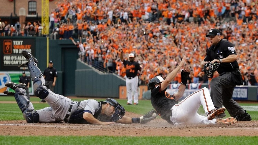 Detroit Tigers catcher Alex Avila, left, reaches but can't make the tag in time as Baltimore Orioles' J.J. Hardy scores on a double by Delmon Young in the eighth inning of Game 2 in baseball's AL Division Series in Baltimore, Friday, Oct. 3, 2014. Baltimore won 7-6. (AP Photo/Patrick Semansky)