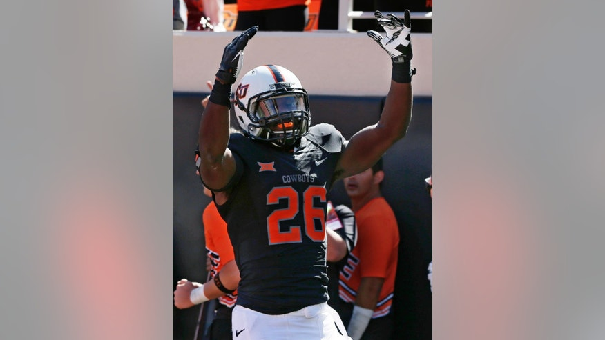 Oklahoma State running back Desmond Roland (26) celebrates after a touchdown in the fourth quarter of an NCAA college football game against Iowa State in Stillwater, Okla., Saturday, Oct. 4, 2014. Oklahoma State won 37-20.  (AP Photo/Sue Ogrocki)