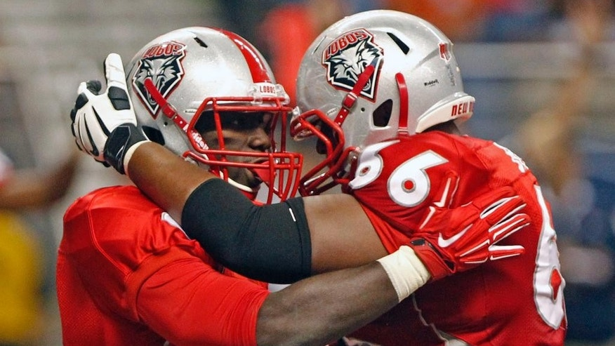 New Mexico running back Cranston Jones, left, is congratulated by LaMar Bratton after scoring a touchdown during the third quarter of an NCAA college football game against UTSA in San Antonio, Texas, Saturday, Oct. 4, 2014. New Mexico won 21-9. (AP Photo/Michael Thomas)