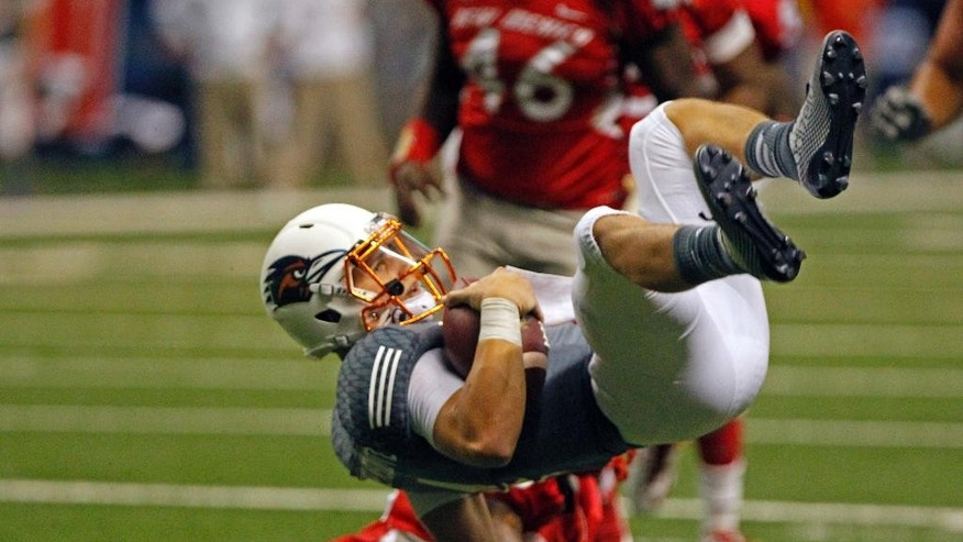 UTSA quarterback Blake Bogenschutz flips after being hit by New Mexico defensive back SaQwan Edwards during the fourth quarter of an NCAA college football game in San Antonio, Texas, Saturday, Oct. 4, 2014. (AP Photo/Michael Thomas)