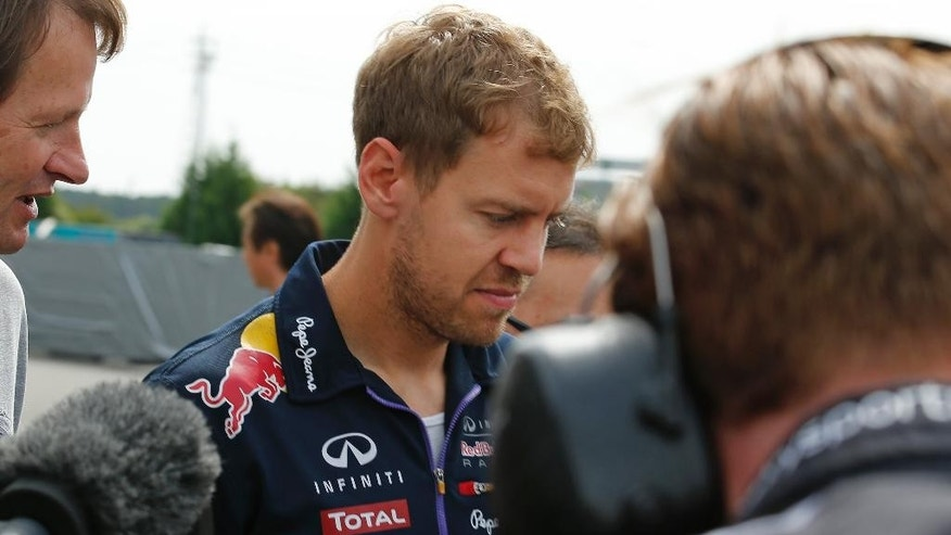 Red Bull Racing driver Sebastian Vettel of Germany is surrounded by the media at the paddock before the third practice session for Sunday's Japanese Formula One Grand Prix at the Suzuka Circuit in Suzuka, central Japan, Saturday, Oct. 4, 2014. Four-time defending champion Vettel will leave Red Bull at the end of the season, with the team expecting him to join Ferrari. (AP Photo/Shuji Kajiyama)