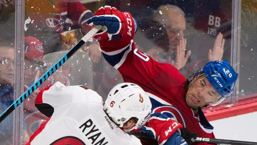 Montreal Canadiens' Manny Malhotra, right, collides with Ottawa Senators' Bobby Ryan during the third period of an NHL preseason hockey game Saturday, Oct. 4, 2014, in Montreal. (AP Photo/The Canadian Press, Graham Hughes)