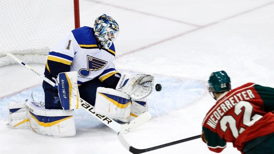 St. Louis Blues goalie Brian Elliott (1) deflects a shot by Minnesota Wild right wing Nino Niederreiter (22), of Switzerland, during the first period of a preseason NHL hockey game in St. Paul, Minn., Saturday, Oct. 4, 2014.(AP Photo/Ann Heisenfelt)