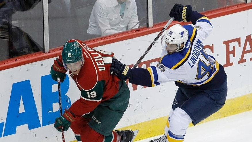 Minnesota Wild center Stephane Veilleux (19) controls the puck in front of St. Louis Blues defenseman Petteri Lindbohm, right, of Finland, during the first period of a preseason NHL hockey game in St. Paul, Minn., Saturday, Oct. 4, 2014.(AP Photo/Ann Heisenfelt)