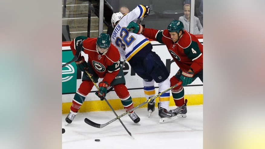 Minnesota Wild defenseman Stu Bickel (4) shoves St. Louis Blues left wing Chris Porter (32) off the puck as Wild center Cody Almond (12) reaches for it during the first period of a preseason NHL hockey game in St. Paul, Minn., Saturday, Oct. 4, 2014.(AP Photo/Ann Heisenfelt)