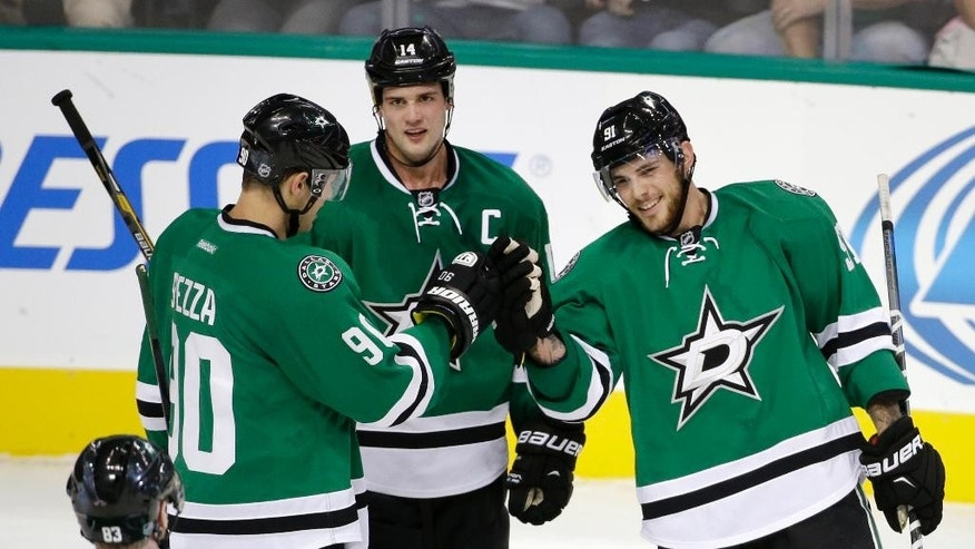 Dallas Stars' Ales Hemsky (83) of Czech Republic, Jason Spezza (90) and Jamie Benn (14) congratulate Tyler Seguin (91) on his goal in the third period of a preseason NHL hockey game against the Florida Panthers, Monday, Sept. 29, 2014, in Dallas. Seguin scored three goals and the Stars rallied to beat the Panthers 5-4. (AP Photo/Tony Gutierrez)