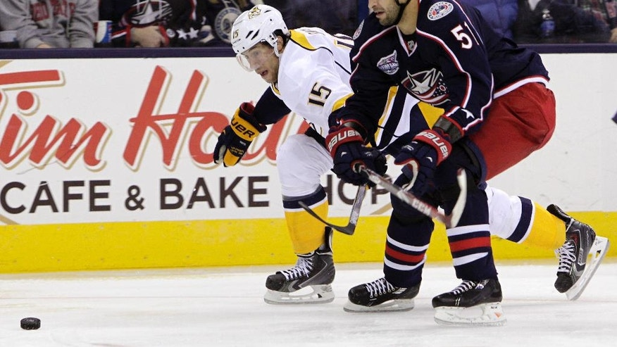Nashville Predators' Craig Smith, left, and Columbus Blue Jackets' Fedor Tyutin, of Russia, chase a loose puck during the third period of a preseason NHL hockey game Saturday, Oct. 4, 2014, in Columbus, Ohio. The Blue Jackets beat the Predators 3-2. (AP Photo/Jay LaPrete)