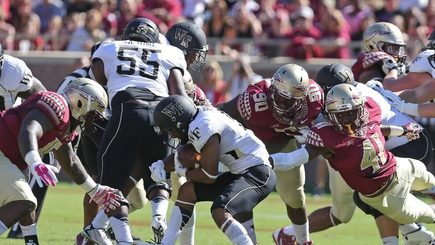 Wake Forest's Orville Reynolds is surrounded by the Florida State defenders Lorenzo Featherson, right, Eddie Goldman, center, and Mario Edwards, left, during the first quarter of an NCAA college football game, Saturday Oct. 4, 2014 in Tallahassee, Fla. (AP Photo/Steve Cannon)