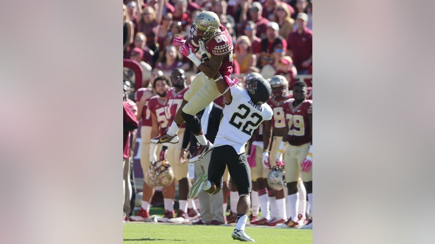 Florida State's Rashad Greene makes a leaping reception despite the defensive effort of Wake Forest's Ryan Janvion during the first quarter of an NCAA college football game, Saturday Oct. 4, 2014 in Tallahassee, Fla. (AP Photo/Steve Cannon)