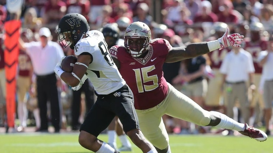 Wake Forest's Jared Crump spins away Florida State's Mario Edwards on a pass play during the first quarter of an NCAA college football game, Saturday Oct. 4, 2014 in Tallahassee, Fla. (AP Photo/Steve Cannon)
