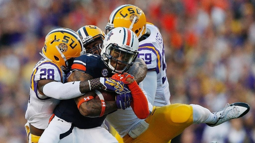 Auburn quarterback Nick Marshall (14) is tackled by LSU safety Jalen Mills (28) and LSU defensive end Jermauria Rasco (59) during the first half of an NCAA college football game Saturday, Oct. 4, 2014, in Auburn, Ala. Auburn won 41-7. (AP Photo/Brynn Anderson)