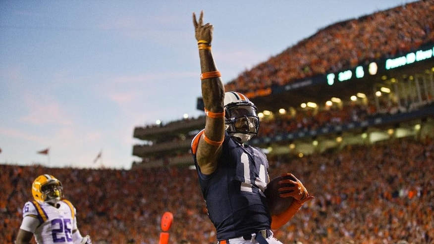 Auburn quarterback Nick Marshall (14) celebrates his touchdown run against LSU in the first half of an NCAA college football game Saturday, Oct. 4, 2014, in Auburn, Ala. (AP Photo/Brynn Anderson)