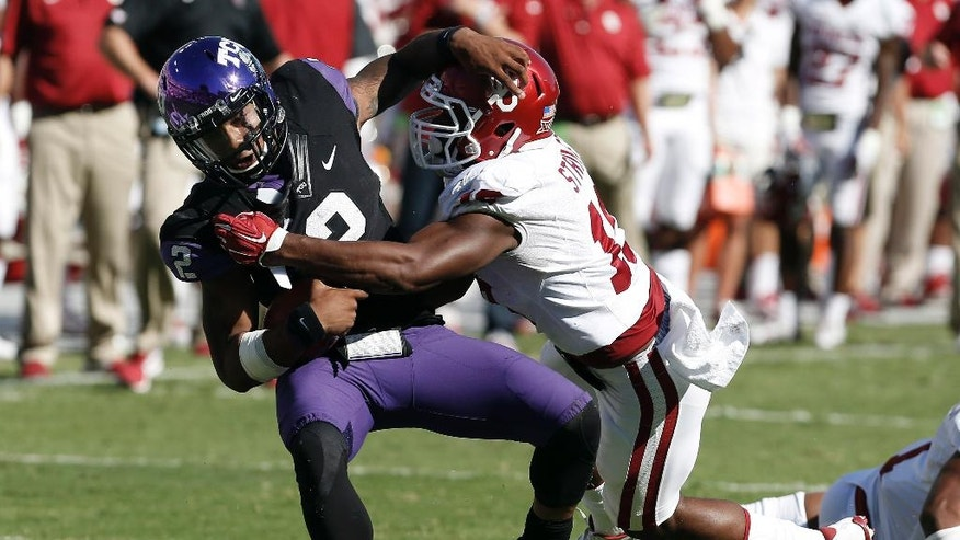 Oklahoma linebacker Eric Striker (19) tackles TCU  quarterback Trevone Boykin (2) during the first half of an NCAA college football game at Amon G. Carter Stadium, Saturday, Oct. 4, 2014, in Fort Worth, Texas. (AP Photo/Brandon Wade)