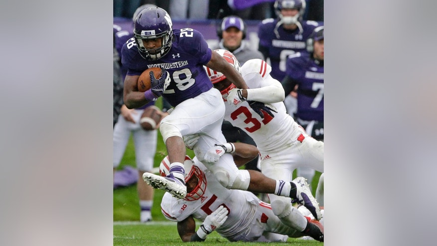Northwestern running back Justin Jackson (28) runs with the ball past Wisconsin cornerback Darius Hillary (5) and safety Lubern Figaro (31) during the first half of an NCAA college football game in Evanston, Ill., Saturday, Oct. 4, 2014. (AP Photo/Nam Y. Huh)