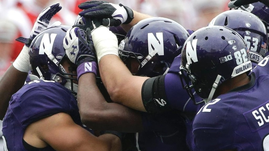 Northwestern super back Dan Vitale (40), left, celebrates with teammates after catching a touchdown pass during the first half of an NCAA college football game against Wisconsin in Evanston, Ill., Saturday, Oct. 4, 2014. (AP Photo/Nam Y. Huh)