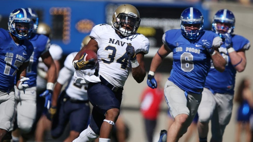 Navy fullback Noah Copeland, center, carries the ball for a long gain as Air Force defensive back Jamal Byrd, left, and linebacker Connor Healy pursue late in the first quarter of an NCAA college football game at Air Force Academy, Colo., on Saturday, Oct. 4, 2014. (AP Photo/David Zalubowski)