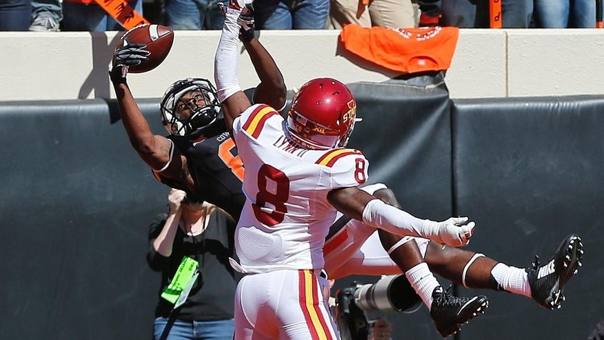 Oklahoma State wide receiver Jhajuan Seales (81) reaches for but can't catch a pass behind Iowa State defensive back Kenneth Lynn (8) in the second quarter of an NCAA college football game in Stillwater, Okla., Saturday, Oct. 4, 2014. (AP Photo/Sue Ogrocki)