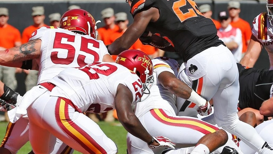 Oklahoma State running back Desmond Roland (26) carries for a touchdown against Iowa State in the second quarter of an NCAA college football game in Stillwater, Okla., Saturday, Oct. 4, 2014. At left are Iowa State defenders Jevohn Miller (55) and T.J. Mutcherson (22). (AP Photo/Sue Ogrocki)