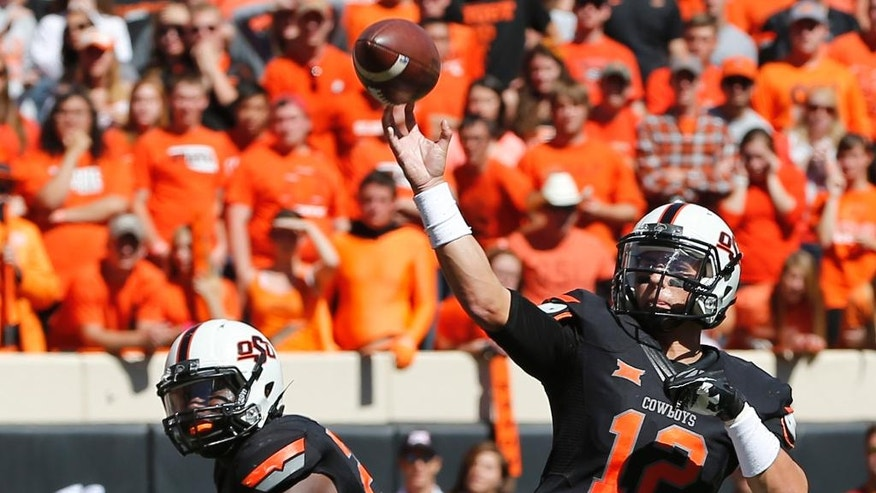Oklahoma State quarterback Daxx Garman (12) passes against Iowa State in the second quarter of an NCAA college football game in Stillwater, Okla., Saturday, Oct. 4, 2014. (AP Photo/Sue Ogrocki)