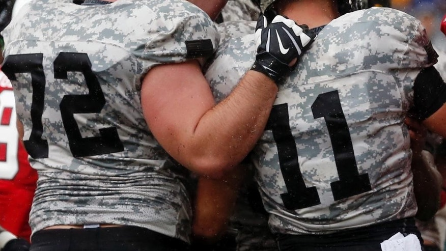 Army quarterback A.J. Schurr (11) celebrates his touchdown against Ball State with teammate Colby Enegren (72) during the first half of an NCAA college football game on Saturday, Oct. 4, 2014, in West Point, N.Y. (AP Photo/Mike Groll)