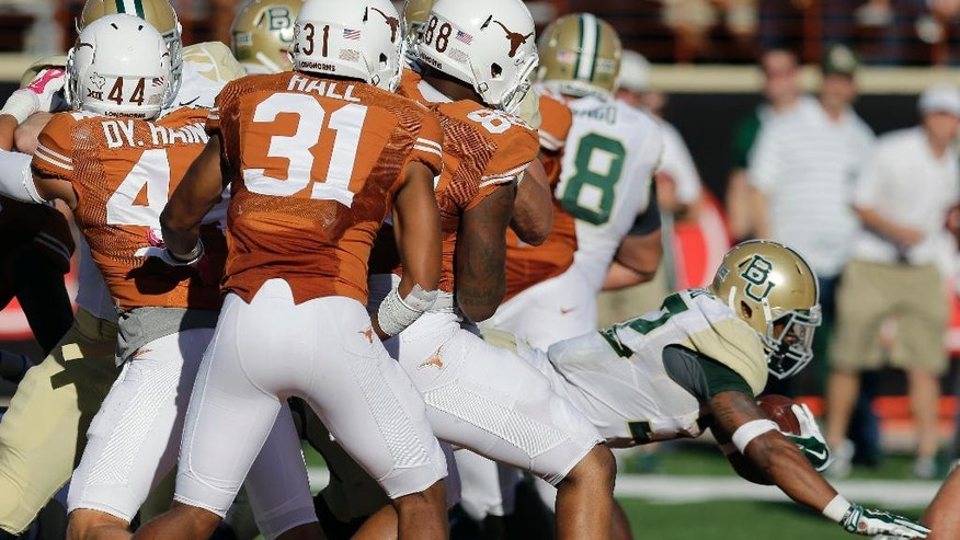Baylor's Shock Linwood (32) dives past Texas defenders for a touchdown during the second half of an NCAA college football game, Saturday, Oct. 4, 2014, in Austin, Texas. (AP Photo/Eric Gay)