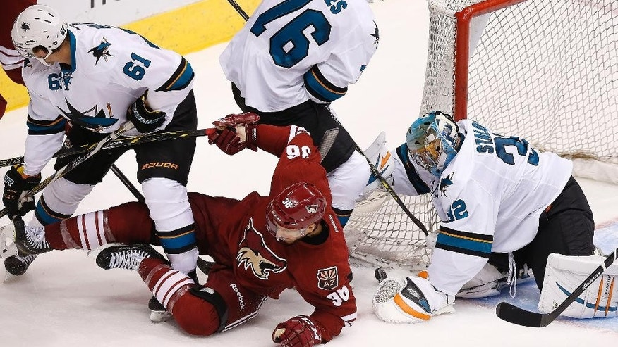 San Jose Sharks' Alex Stalock (32) makes a save on a shot by Arizona Coyotes' Rob Klinkhammer (36) as Sharks' Eriah Hayes (76) and Justin Braun (61) converge to defend during the second period of a preseason NHL hockey game Friday, Oct. 3, 2014, in Glendale, Ariz. (AP Photo/Ross D. Franklin)