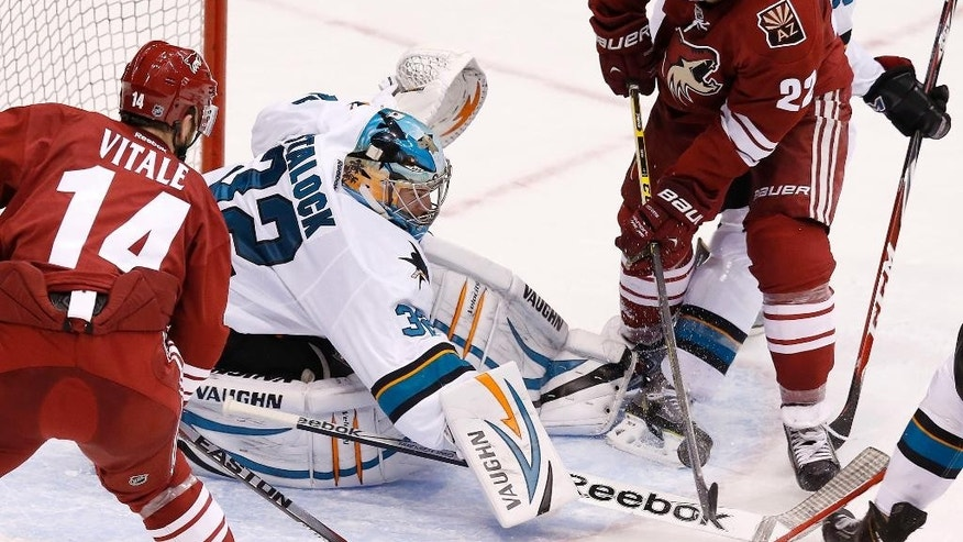 San Jose Sharks' Alex Stalock (32) tries to control the puck in front of the net as Arizona Coyotes' Brandon McMillan (22) and Joe Vitale (14) move in during the second period of a preseason NHL hockey game Friday, Oct. 3, 2014, in Glendale, Ariz. (AP Photo/Ross D. Franklin)
