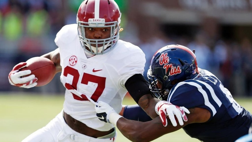 Alabama running back Derrick Henry (27) is tackled by Mississippi defensive end C.J. Johnson (10) during the first quarter of an NCAA college football game in Oxford, Miss., Saturday, Oct. 4, 2014. (AP Photo/Rogelio V. Solis)