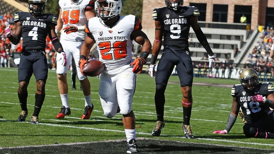 Oregon State running back Terron Ward (28) scores a touchdown against Colorado in the first half of an NCAA college football game in Boulder, Colo., Saturday, Oct. 4, 2014. (AP Photo/Brennan Linsley)