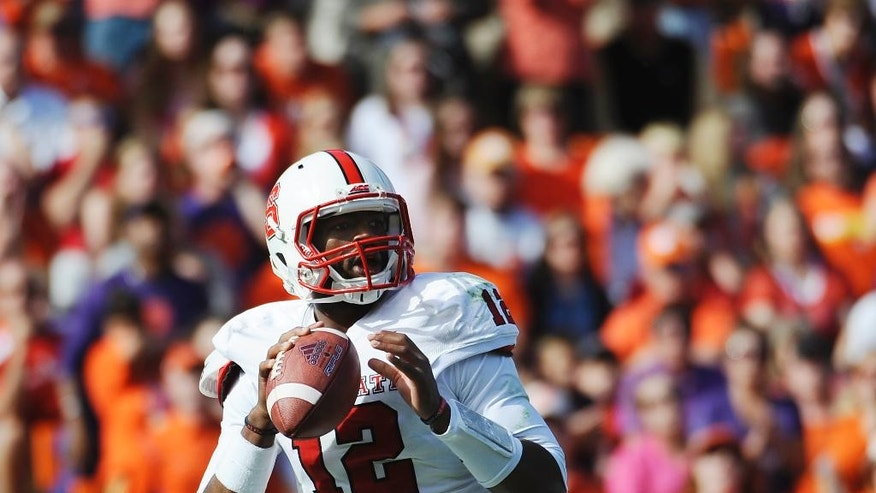 North Carolina State quarterback Jacoby Brissett (12) looks to pass against Clemson during the first half of an NCAA college football game, Saturday, Oct. 4, 2014, in Clemson, S.C. (AP Photo/Rainier Ehrhardt)