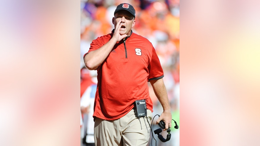 North Carolina State head coach Dave Doeren gives instructions on the sideline during the first half of an NCAA college football game against Clemson, Saturday, Oct. 4, 2014, in Clemson, S.C. (AP Photo/Rainier Ehrhardt)